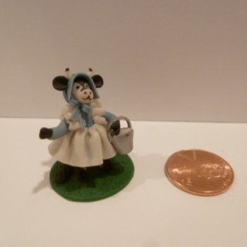 Clay Cow figurine wearing a dress